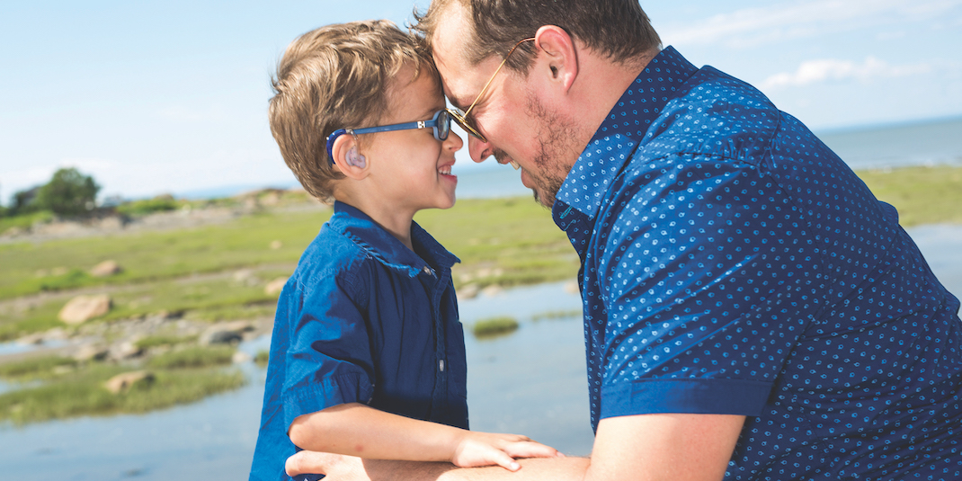 Boy with hearing aides alongside father
